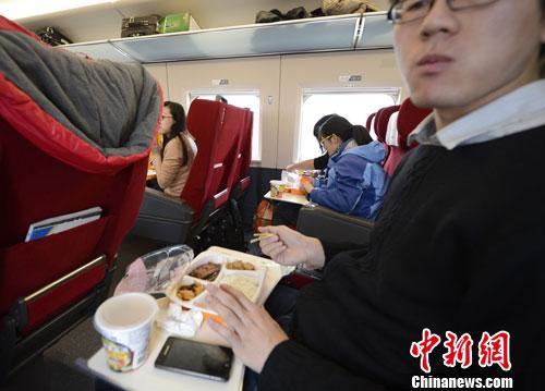 资料图:图为动车组乘客在品尝列车提供的餐食。<a target='_blank' href='http://www.chinanews.com/'>中新社</a>发 侯宇 摄