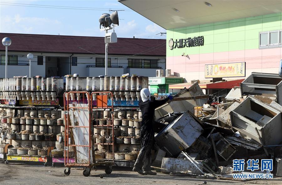 7月10日,在日本冈山县仓敷市真備町一家超市前,工作人员在整理浸过水的货物。日本西部地区连降特大暴雨,引发30多年来最严重水灾。据日本媒体汇总,截至7月10日上午,已有至少130人丧生,将近60人失联。新华社记者 马平摄