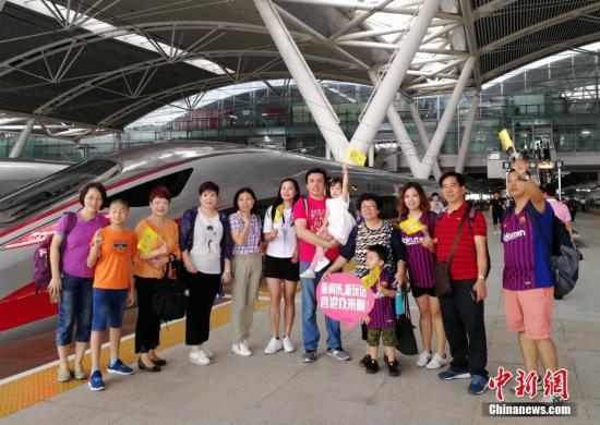 """9月23日一大早,广州南站,由49名广州游客组成的""""首发团""""搭乘8时30分的G6523次高铁列车前往香港西九龙站,他们将在香港海洋公园等地游玩,或购物、探亲、会友,度过一个难忘的中秋佳节。当日,广深港高铁全线开通运营。"""