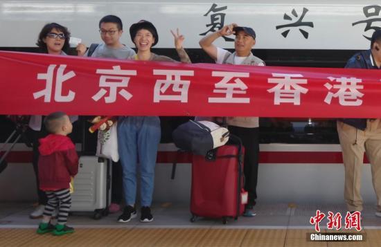 """9月23日,北京西开往香港西九龙的G79次""""复兴号""""高铁列车在北京西站首发。图为旅客在首发列车前拍照。 <a target='_blank' >中新社</a>记者 贾天勇 摄"""